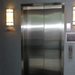 Brush stainless header and jamb cladding at elevator in lobby of 8251 Maryland